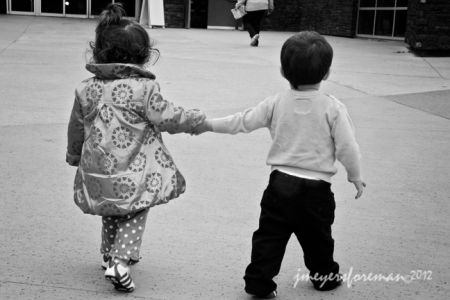 two small children holding hands as they walk